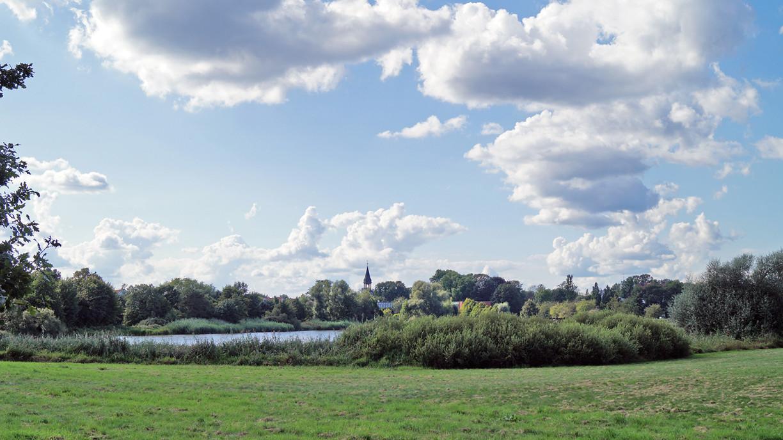 Blick über den Schlosssee auf den Kirchturm der St-Nicolai-Kirche