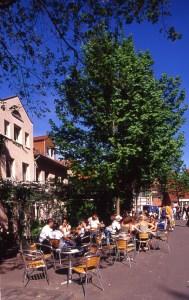 Viele Gäste auf der sonnigen Terrasse eines Cafés am Wochenmarkt