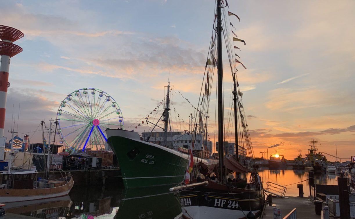 Im Fischereihafen Bremerhaven sind ein Segelschiff und zwei Motorschiffe zu sehen. Auch sieht man ein Riesenrad und einen Leuchtturm. Sonnenuntergänge in Bremerhaven