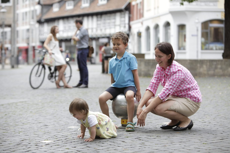 Unterwegs mit Kindern in Braunschweig: Kleines Mädchen krabbelt auf dem Domplatz, kleiner Junge sitzt auf einer eisernen Kugel der Spielfährte. Die Mutter hockt neben den beiden.