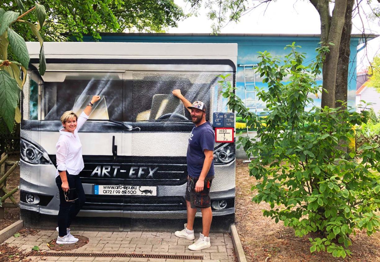 Kerstin Hecker und Simon Pape vor einer Trafostation, als Wohnmobil bemalt