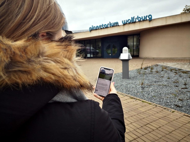 Frau nutzt App CultureMaps vor Planetarium
