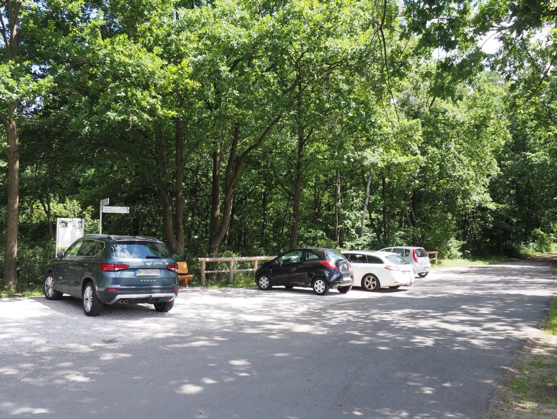 Ein Parkplatz mit Infotafel und Sitzbank am Startpunkt des Wanderweges.
