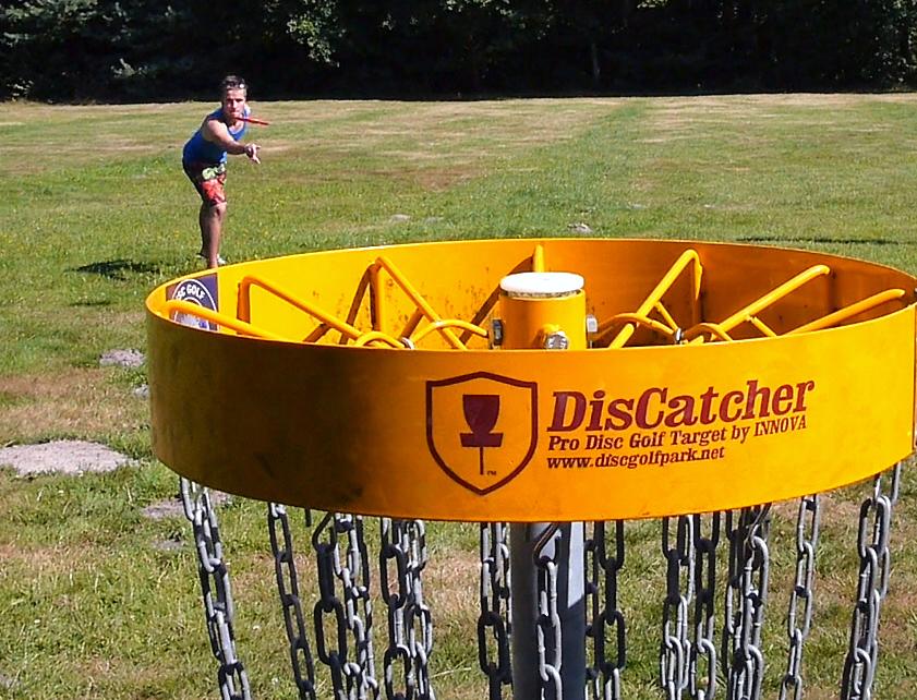 Mann zielt mit Frisbeescheibe auf Disc-Golf-Korb