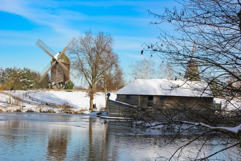 Schiffsmühle und Bockwindmühle unter blauem Himmel in Schneelandschaft