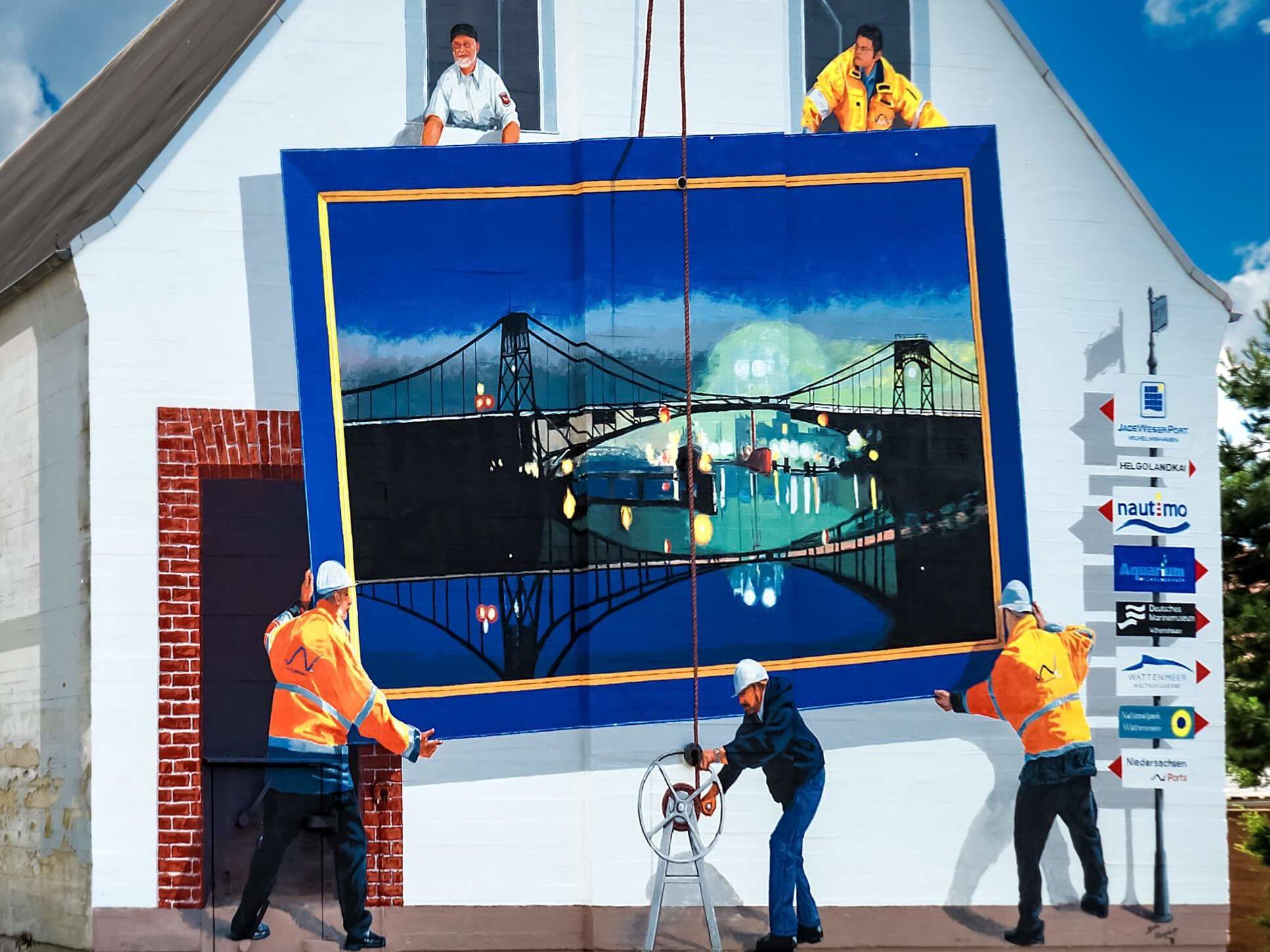 Fassadengemälde von Buko Königshoff. Zu sehen ist ein Bild im Bild, die Kaiser-Wilhelm-Brücke als Bild wird von Arbeitern aufgehängt.