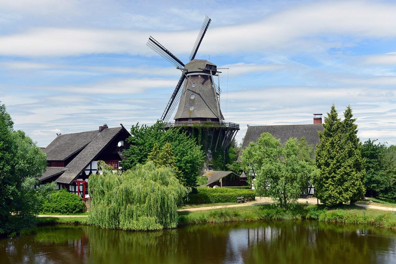 Windmühle und Fachwerkhaus an einem See mit grünen Bäumen