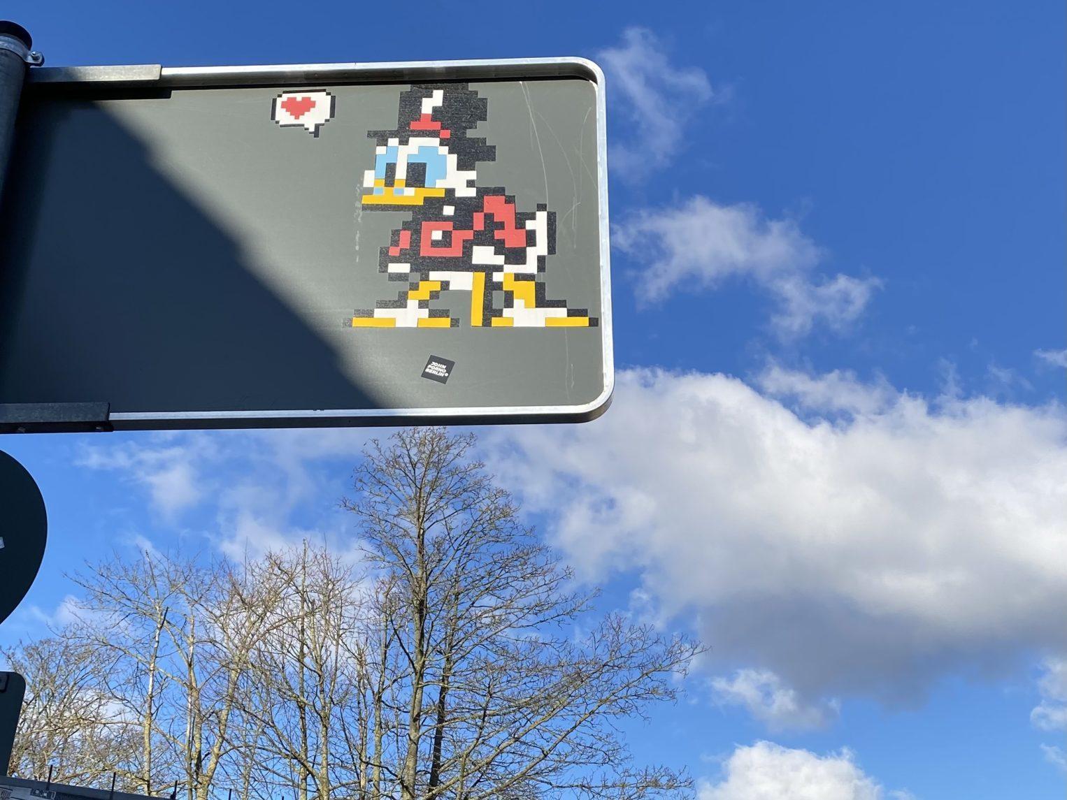 Pixel Art von Dagobert Duck an der Rückseite eines Verkehrsschildes.