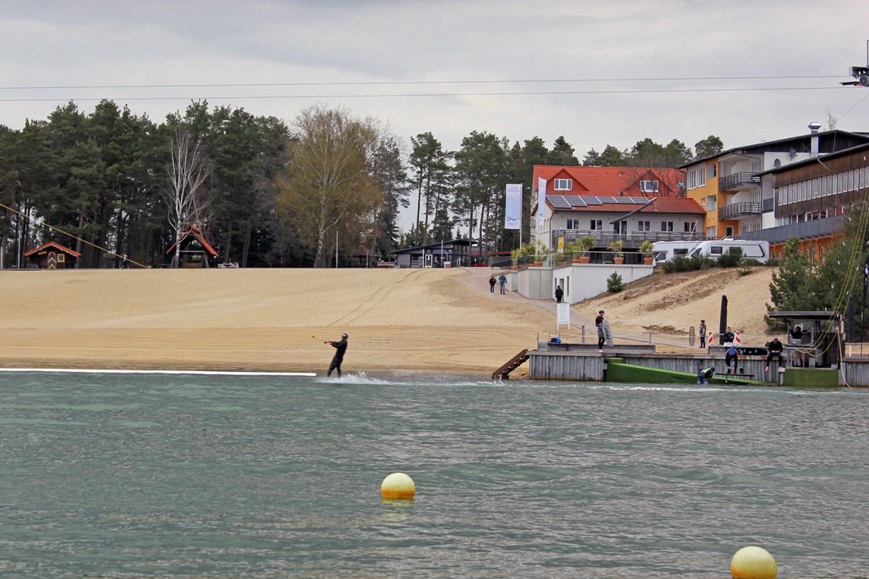 Wakeboardfahrer vor der Kulisse des Strands und des Hotels am Bernsteinsee