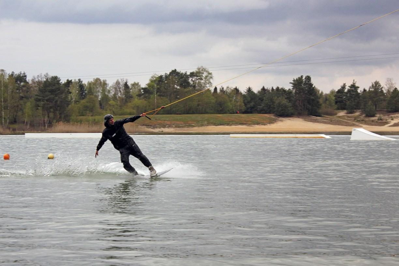 Wakeboardfahrer mit einer Hand am Zugseil am Bernsteinsee