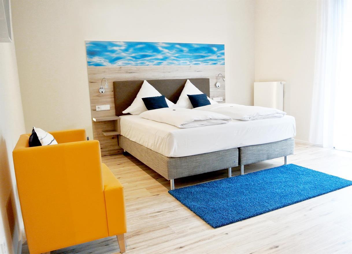 Doppelbett und Sessel in einem Hotelzimmer am Bernsteinsee