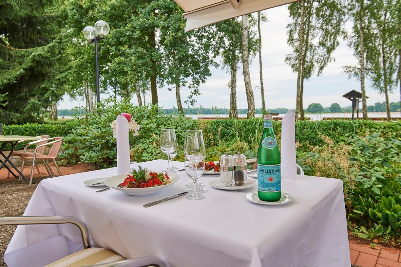 Terrasse des Seehotels am Tankumsee mit Tisch mit weißer Dischdecke, Salattellern, Gläsern und Wasserflasche und Blick auf See