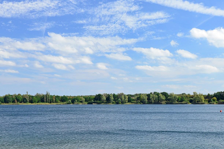 Blick über den Tankumsee ans gegenüberliegende Ufer mit Bäumen unter blauem Himmel