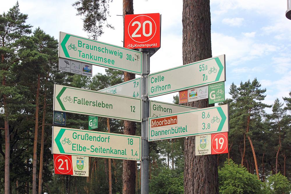 Pfahl mit sieben Hinweisschilder für Fahrradfahrer und einem Knotenpunkt