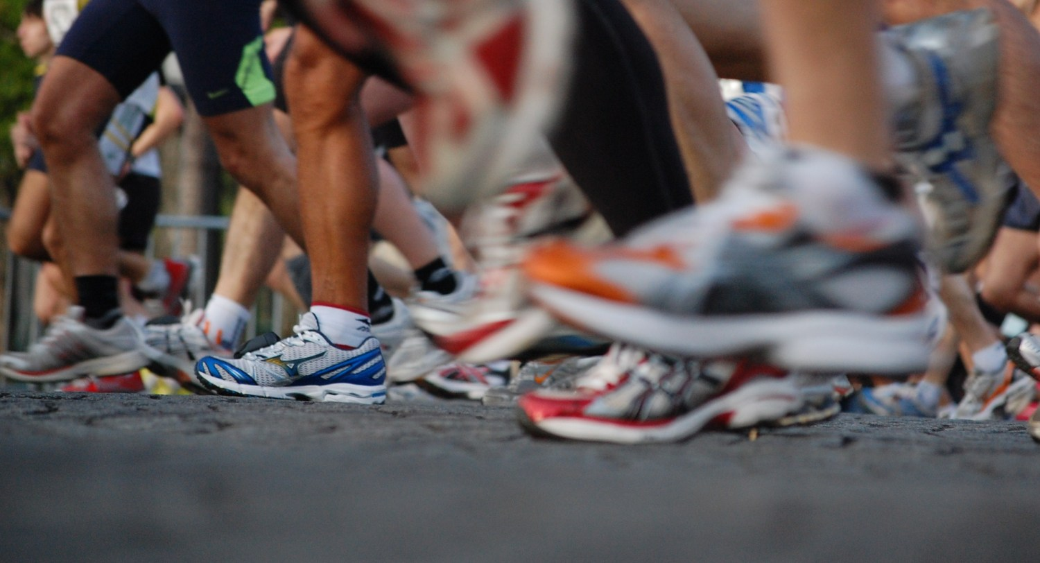 A running club takes off at the start of a tempo run.