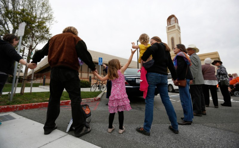 """Evelyn Peters, center left, 4, from Mountain View, reaches for her sisters, Elena, 2, hand as they participate in """"Hands Around the Mosque"""" with their parents Steve, left, and Teresa, outside of the Muslim Community Association in Santa Clara, Calif. on Sunday, March 19, 2017. (Nhat V. Meyer/Bay Area News Group)"""
