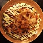 Okonomiyaki in dish, topped with flakes