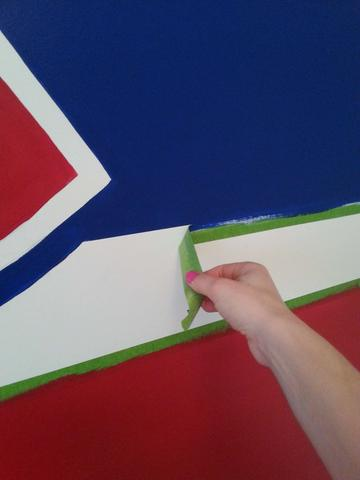 Peeling painter's tape off of the Montreal Canadiens mural painted by Adrienne of AboutMurals.ca
