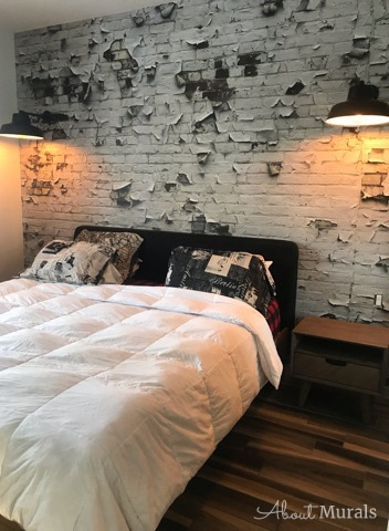 A gritty brick wallpaper in a bedroom with industrial lights and a white bed, from AboutMurals.ca