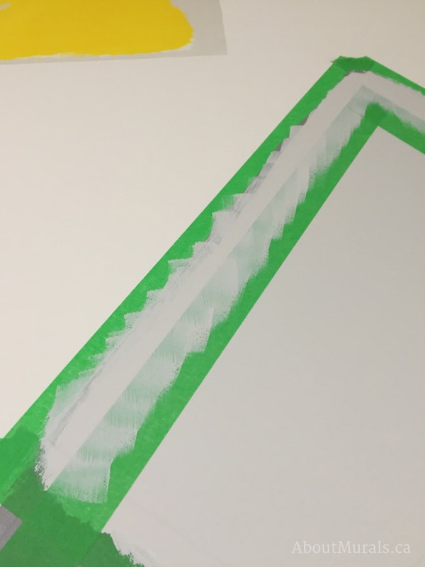 A narrow gap is created with painters tape to outline a mountain mural