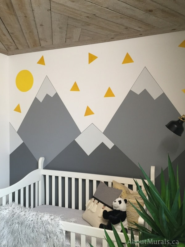 A mountain mural nursery painted by Adrienne of AboutMurals.ca for the Holmes Next Generation TV show sits behind a baby's crib