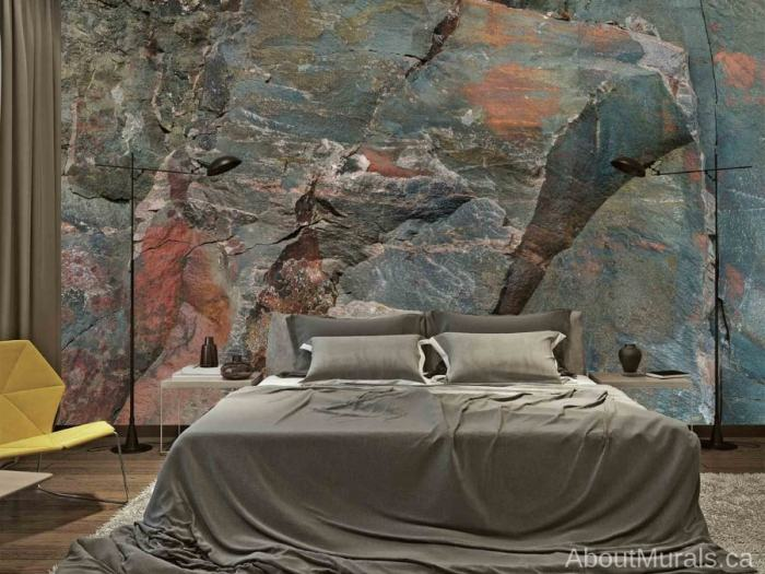 A grey bed sits in front of a Canadian Shield Rock Face wallpaper, sold by AboutMurals.ca