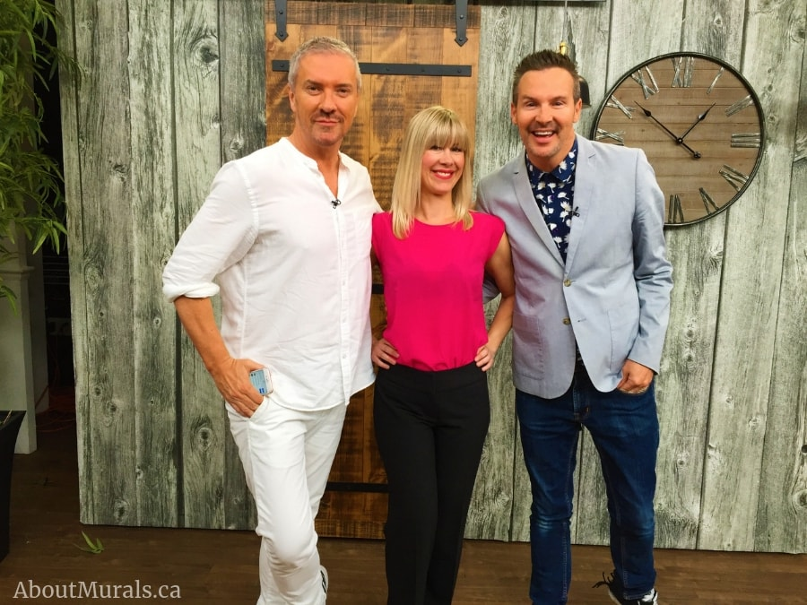 Adrienne of AboutMurals.ca stands with Colin and Justin in front of her wood look wallpaper on set at Cityline