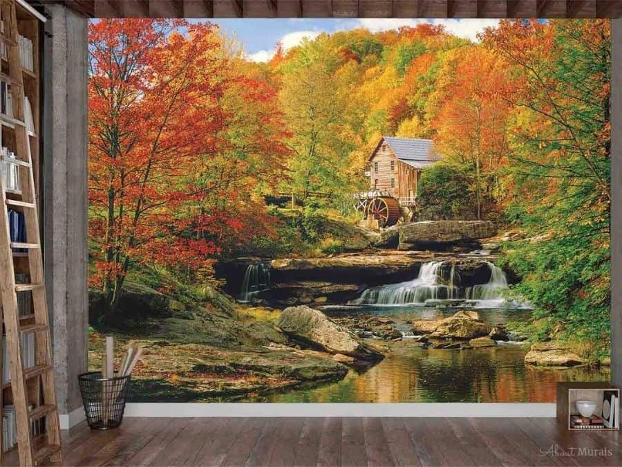 Watermill Wallpaper, as seen on the wall of this office, adds blazing colour and a historic feeling to walls with Glade Creek Grist Mill against fall trees. Autumn forest wallpaper sold by AboutMurals.ca.