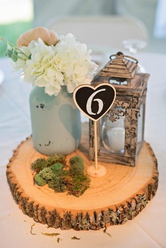lantern-wedding-centerpiece-on-a-wooden-piece-of-lantern-flowers-in-a-jar-of-moss-and-a-table-number-bentley-photography-via-instagram-334x500