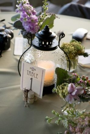 lantern-wedding-centerpiece-round-lantern-with-a-candle-and-a-table-number-surrounded-by-flowers-brent-gulledge-photography-334x500