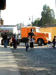 A large semi turns into the street in contrast with the woman carrying firewood