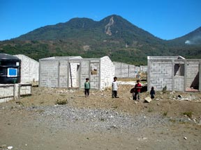 Cement block homes for refuges from the landslide shown on the mountain in the background