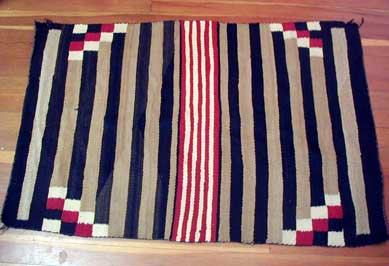Saddle blanket with black, tan, and red stripes and blocks