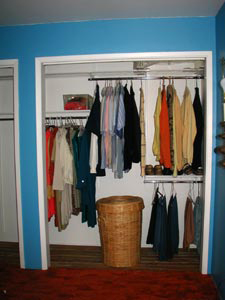 Closet with clothes hanging in it