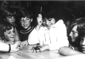 Young girl with tarantula crawling over hand while other children look on