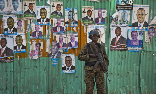 A Ugandan soldier stands guard in front of posters for opposition leader Kizza Besigye and candidates for parliamentary elections, in an area that saw violence after Besigye was arrested, in Kampala, Uganda Friday, Feb. 19, 2016. Police in Uganda arrested opposition leader Kizza Besigye at his party's headquarters Friday after heavily armed police surrounded the building and fired tear gas and stun grenades at his supporters who took to the streets. (AP Photo/Ben Curtis)