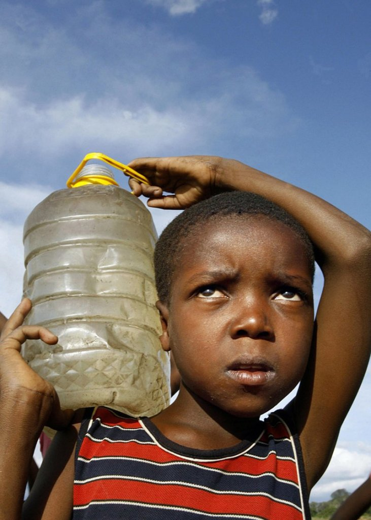 7 December 2008: A boy carries water for domestic use he fetched from an untreated well which has been a major source of cholera in Harare, ZimbabweDesmond Kwande/ AFP