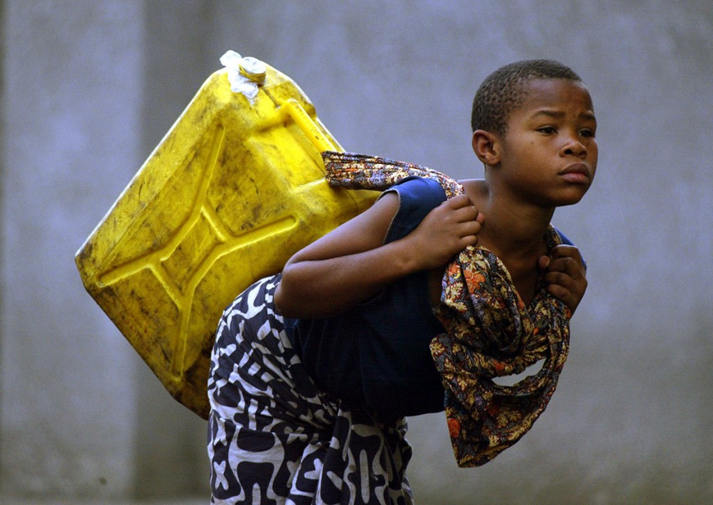 25 January 2002: A girl carries potable water to her home in GomaPedro Ugarte/ AFP