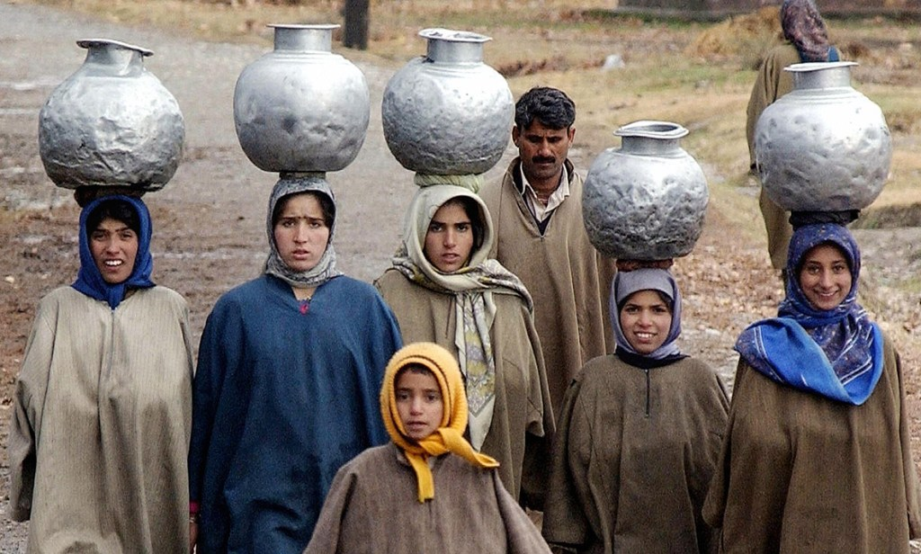 2 December 2004: Indian Kashmiri girls carry water pots on their heads in the outskirts of Srinagar, KashmirSajjad Husaain/ AFP