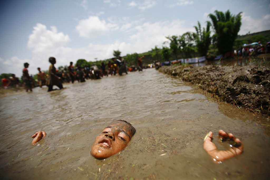 29 June 2012: A boy lies in muddy water in Pokhara valley, west of Nepal's capital KathmanduNavesh Chitrakar/ Reuters
