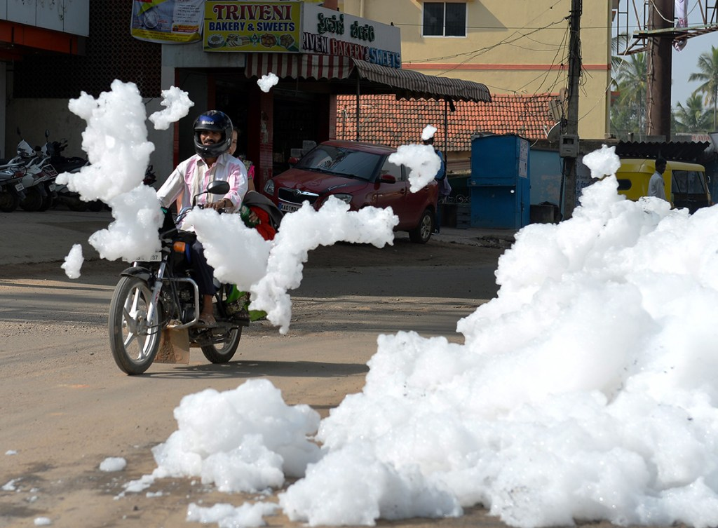 1 May 2015: A motorcyclist negotiates away from piles of foam at Varthur Kodi junction situated in east Bangalore. The innocuous-looking foam is toxic effluent caused by the polluted sewage water overflowing from nearby Varthur LakeManjunath Kiran/ AFP