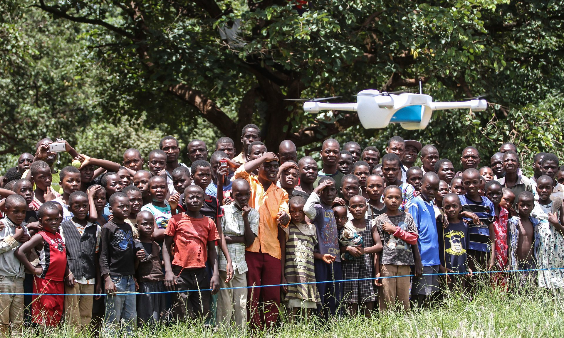 Children look on in astonishment as a drone is put through its paces at a community demonstration in Lilongwe. The Malawian government could use drones to reduce waiting times for medical tests. Photograph: Bodole/Unicef