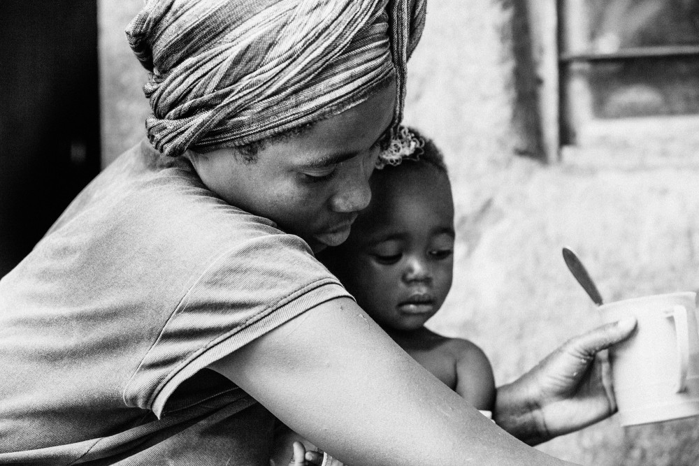 Esther holding her child as she prepares a meal of soy flour & water outside her home.