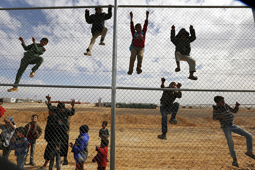 SPECTATORS: Children climb a fence to watch a football training workshop in Azraq refugee camp in Jordan last November. REUTERS/Muhammad Hamed