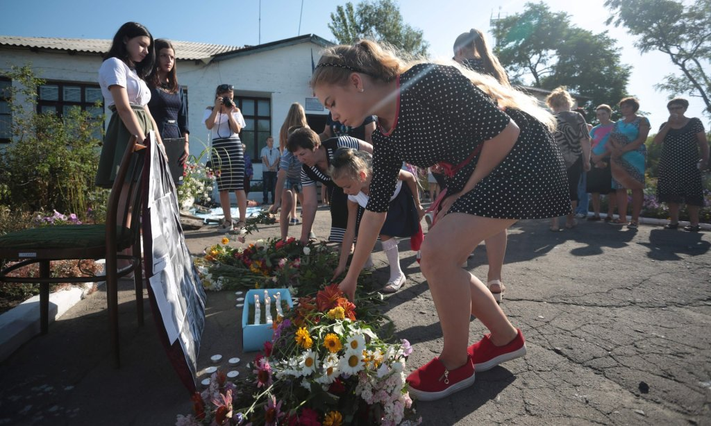 Local villagers lay flowers near pictures of the passengers on flight MH17 flight at a makeshift memorial in Petropavlivka village in eastern Ukraine on Sunday. Photograph: Aleksey Filippov/AFP/Getty Images