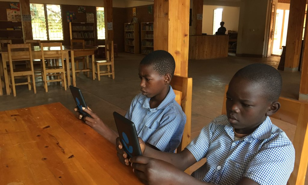 John Kanyambo and Dany Tuyizere, both 12, at a library which where e-readers have been made available thanks to a charity. Photograph: Mark Rice-Oxley for the Guardian