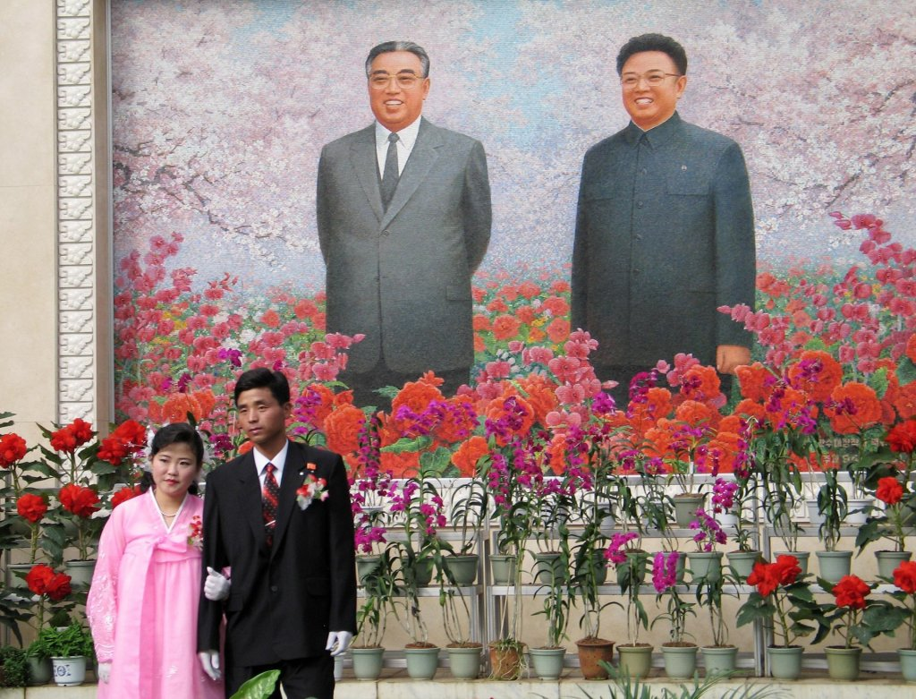 A couple pose in front of the country's founder Kim Il-Sung and his more romantic son Kim Jong-il Photograph: Reuters