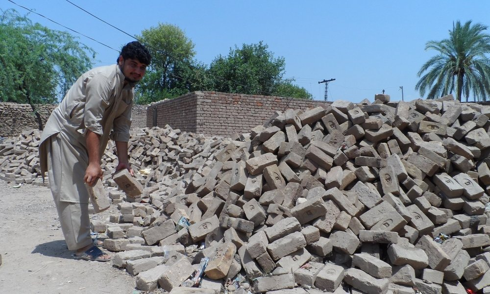 Aamir Faheem with bricks he plans to use to repair his home, which was damaged by fighting in Piple Garhi, a village in Pakistan's federally administered tribal areas. Photographs: Aamir Saeed/Irin