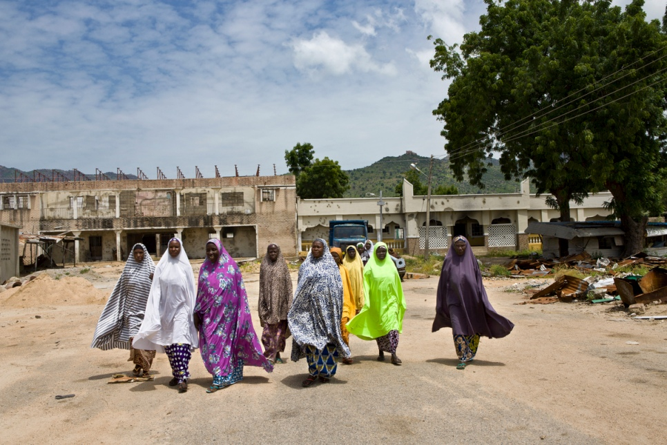 A group of women walk along a street in front of the bombed out ruins of what was the Emir's palace in Gwoza, Nigeria. © UNHCR/Hélène Caux