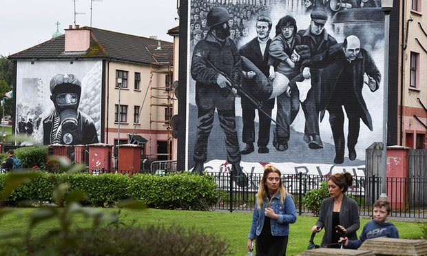 A family in Londonderry, Northern Ireland, walks past a mural depicting the events of Bloody Sunday. Photograph: Charles McQuillan/Getty Images